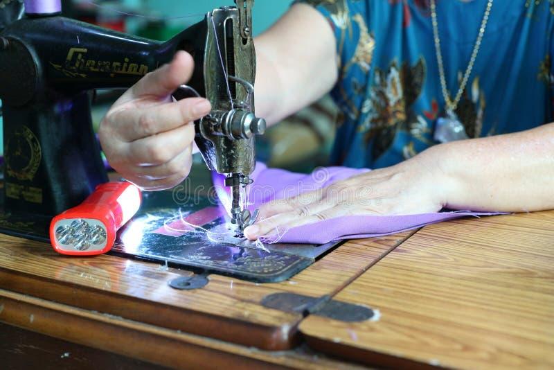 Κλείστε επάνω το ασιατικό χέρι γυναικών συλλαμβάνοντας τα λεπτά υφάσματα, πορφύρα, ράψιμο, που κόβει το εκλεκτής ποιότητας σχέδιο στοκ φωτογραφία με δικαίωμα ελεύθερης χρήσης