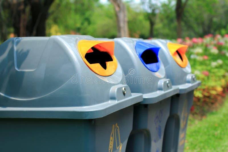 Κλείστε επάνω το γκρίζο ανακύκλωσης δοχείο στο πάρκο και την περιοχή καθαρισμού στοκ φωτογραφία με δικαίωμα ελεύθερης χρήσης
