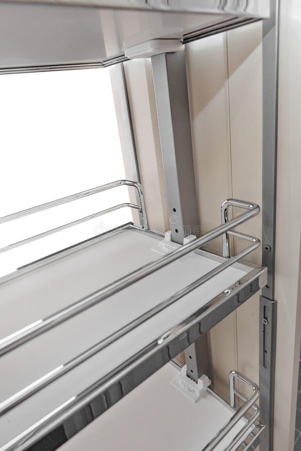 Κλείστε επάνω το εγχώριο εσωτερικό Κουζίνα - ανοιγμένη πόρτα με το ράφι επίπλων χρωμίου Υλικό, σύγχρονο σχέδιο ξύλου και χρωμίου στοκ εικόνα