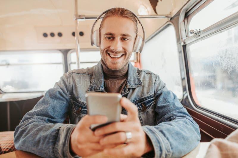 Κλείστε επάνω το ευτυχές αρσενικό στα ακουστικά και το smartphone στοκ φωτογραφίες με δικαίωμα ελεύθερης χρήσης