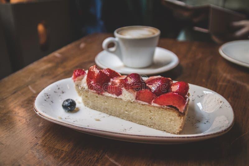 Κλείστε επάνω το κέικ φραουλών με τον καφέ latteon ένας ξύλινος εκλεκτής ποιότητας πίνακας στοκ φωτογραφίες με δικαίωμα ελεύθερης χρήσης