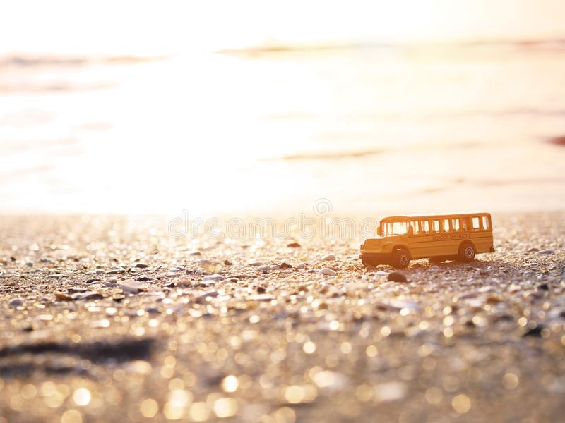 Κλείστε επάνω το κίτρινο παιχνίδι σχολικών λεωφορείων στην άμμο στην παραλία ηλιοβασιλέματος στοκ φωτογραφία