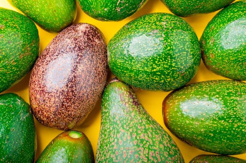 Κλείστε επάνω το κόκκινο οργανικό αβοκάντο στην ομάδα πράσινων υγιών τροφίμων αβοκάντο στο κίτρινο επιτραπέζιο υπόβαθρο σύγχρονοι στοκ εικόνες