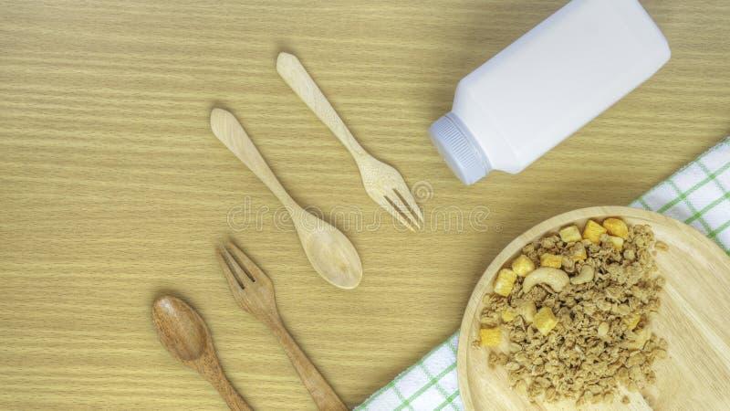 Κλείστε επάνω το κύπελλο granola με ένα ξύλινο κουτάλι και το πιάτο σε ένα ξύλινο επιτραπέζιο υπόβαθρο r απομονωμένος στο λευκό Έ στοκ εικόνα με δικαίωμα ελεύθερης χρήσης