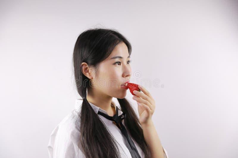 Κλείστε επάνω το λευκό κενό ασιατικό κινεζικό κορίτσι υποβάθρου που η νέα γυναίκα τρώει την υγιή ισορροπημένη ζωή φραουλών φρούτω στοκ φωτογραφία με δικαίωμα ελεύθερης χρήσης