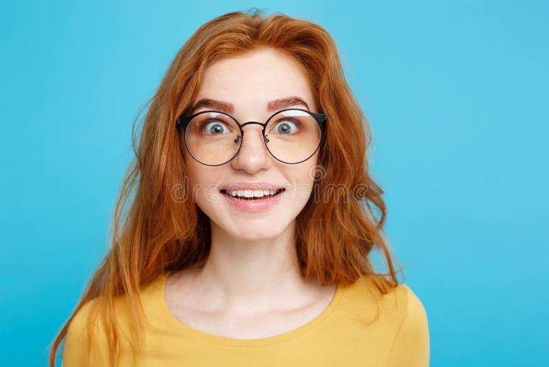 Κλείστε επάνω το νέο όμορφο ελκυστικό κορίτσι redhair πορτρέτου με eyeglass να συγκλονίσει με κάτι Μπλε υπόβαθρο κρητιδογραφιών στοκ εικόνα
