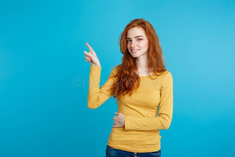 Κλείστε επάνω το νέο όμορφο ελκυστικό κορίτσι redhair πορτρέτου ευχαριστημένο από κάτι και δείχνοντας το δάχτυλο Μπλε κρητιδογραφ στοκ εικόνα με δικαίωμα ελεύθερης χρήσης