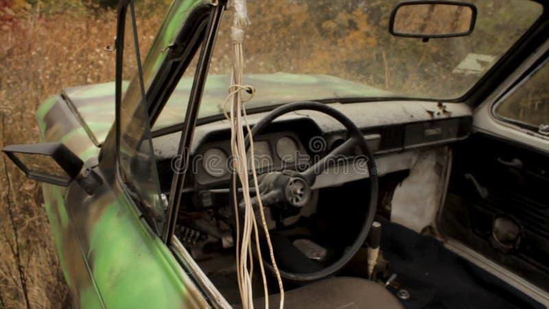 Κλείστε επάνω το παλαιό οξυδωμένο πράσινο αυτοκίνητο στη σύσταση της ψηλής μαραμένης χλόης πλάνο Το εσωτερικό του παλαιού επιβάτη στοκ εικόνα με δικαίωμα ελεύθερης χρήσης