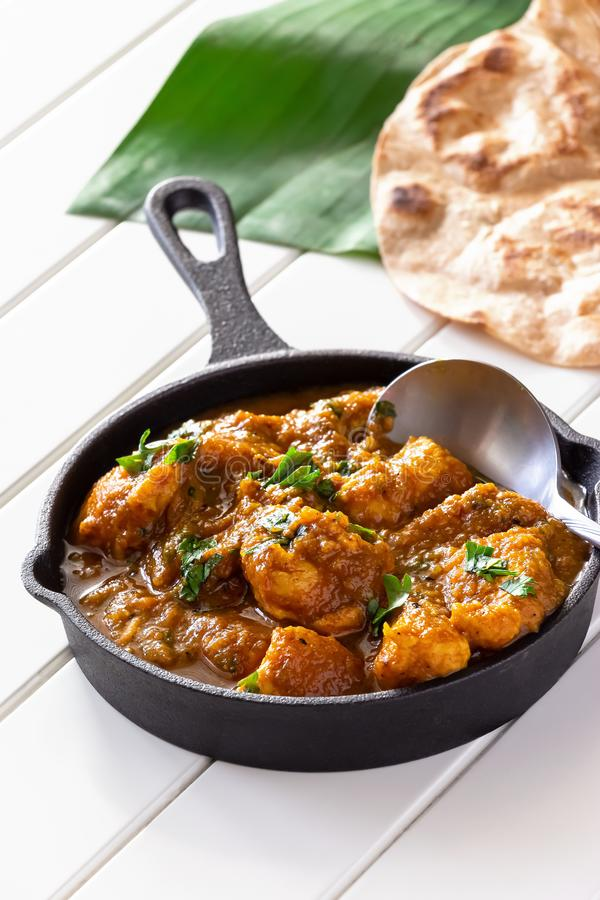 Κλείστε επάνω το παραδοσιακά ινδικά βουτύρου κάρρυ και το λεμόνι κοτόπουλου που εξυπηρετούνται με chapati το ψωμί στο σίδηρο χυτό στοκ φωτογραφία