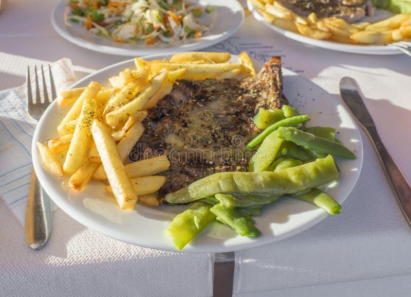 Κλείστε επάνω το πιάτο με το παραδοσιακό σπιτικό ελληνικό γεύμα, ψημένη στη σχάρα μπριζόλα χοιρινού κρέατος με τις τηγανιτές πατά στοκ εικόνα με δικαίωμα ελεύθερης χρήσης