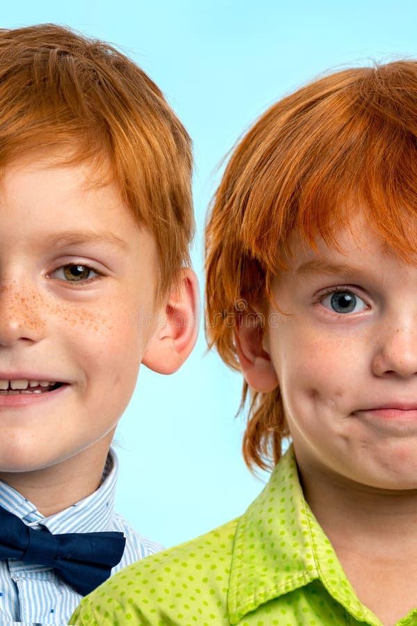 Κλείστε επάνω το πορτρέτο δύο μισών ενός θετικού χαμογελώντας τα redhead αγόρια στο μπλε υπόβαθρο Halfface στοκ εικόνα
