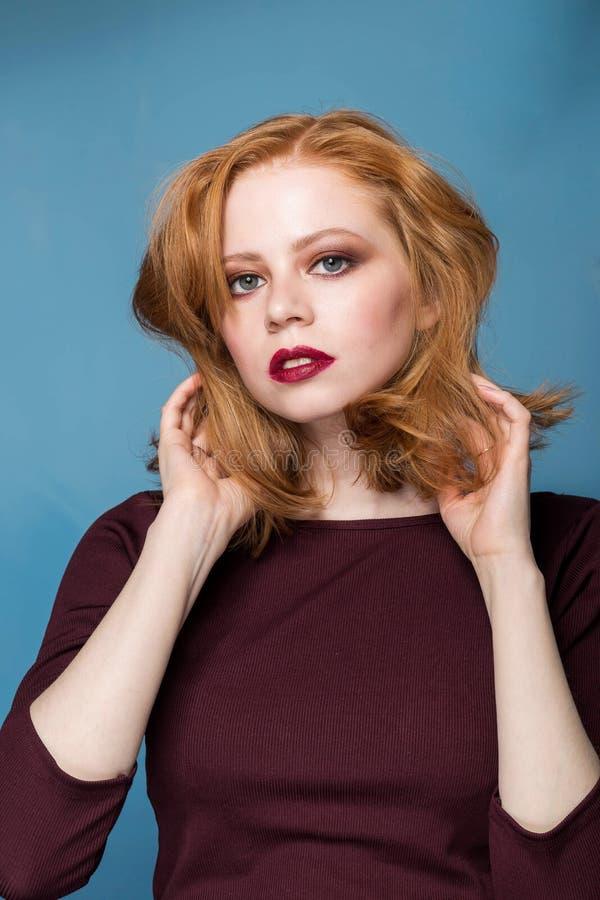 Κλείστε επάνω το πορτρέτο ενός redhead κοριτσιού στο μπλε υπόβαθρο Όμορφη γυναίκα με το επαγγελματικό makeup, Μόδα, μόδα, ομο στοκ φωτογραφίες