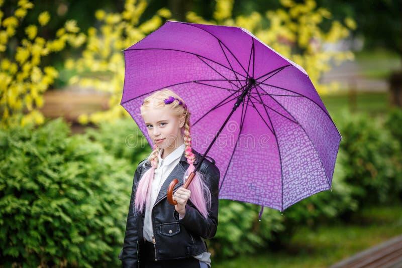 Κλείστε επάνω το πορτρέτο λίγου όμορφου μοντέρνου κοριτσιού παιδιών με μια ομπρέλα στη βροχή στο πάρκο στοκ φωτογραφίες με δικαίωμα ελεύθερης χρήσης
