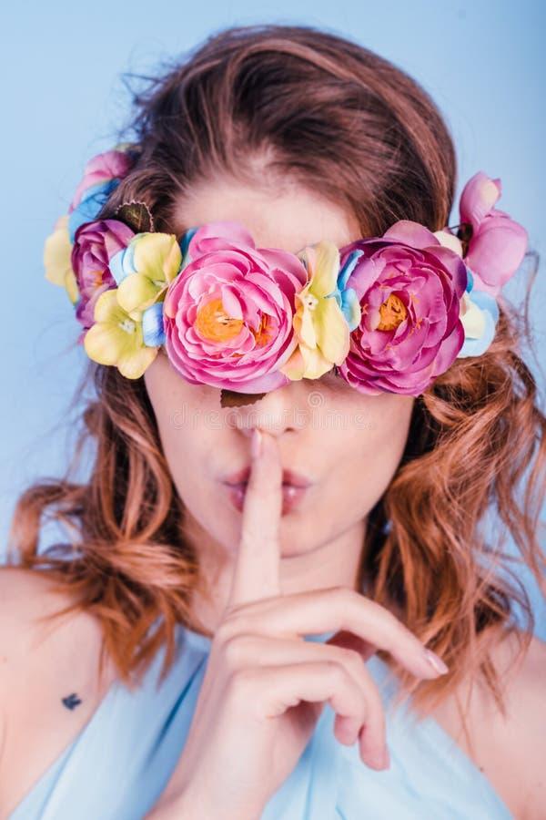 Κλείστε επάνω το πορτρέτο μιας όμορφης ξανθής νέας γυναίκας με το στεφάνι λουλουδιών στα μάτια της και ενός χεριού κοντά στα χείλ στοκ εικόνες