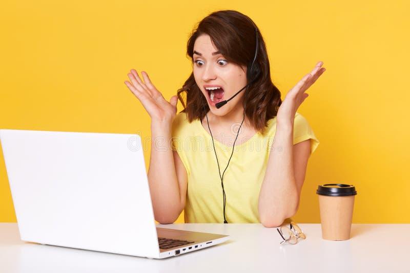 Κλείστε επάνω το πορτρέτο της γοητευτικής συνεδρίασης χειριστών γυναικών στον πίνακα με το κίτρινο υπόβαθρο laptopon στο στούντιο στοκ εικόνα με δικαίωμα ελεύθερης χρήσης
