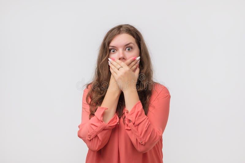 Κλείστε επάνω το πορτρέτο της ελκυστικής, καυκάσιας γυναίκας στο κόκκινο πουκάμισο που κλείνει το πρόσωπό της με τα δάχτυλα Ανησυ στοκ φωτογραφίες με δικαίωμα ελεύθερης χρήσης