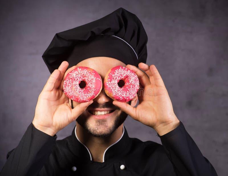 Κλείστε επάνω το πορτρέτο της ευτυχούς χαριτωμένης κουζίνας αρχιμαγείρων με τα γλυκά donuts στοκ εικόνες
