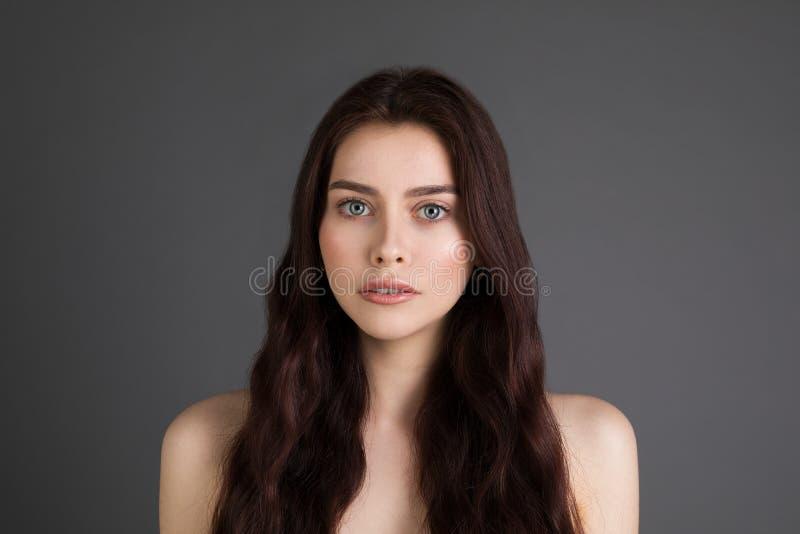 Κλείστε επάνω το πορτρέτο της θαυμάσιας νέας γυναίκας με τη μακροχρόνια τρίχα bronette και τα μεγάλα μπλε μάτια στοκ εικόνες