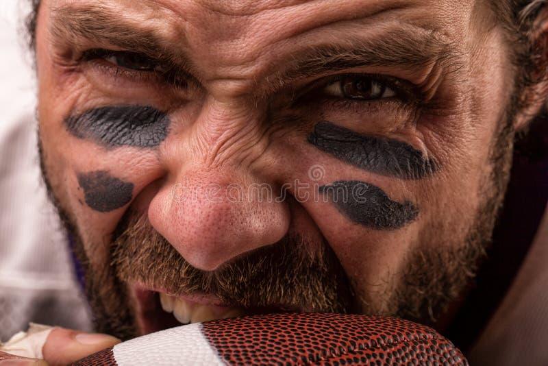 Κλείστε επάνω το πορτρέτο του επιθετικού επιθετικού φορέα φορέων αμερικανικού ποδοσφαίρου δαγκώνοντας τη σφαίρα του στοκ φωτογραφία