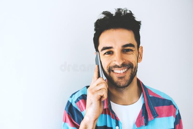 Κλείστε επάνω το πορτρέτο του καυκάσιου όμορφου ατόμου χρησιμοποιώντας και μιλώντας στο κινητό τηλέφωνο, απολαμβάνοντας την επιτυ στοκ εικόνες