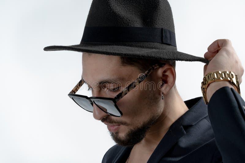 Κλείστε επάνω το πορτρέτο του νέου γενειοφόρου σοβαρού ατόμου στο μαύρο κοστούμι και το καπέλο πέρα από το άσπρο υπόβαθρο στοκ φωτογραφίες