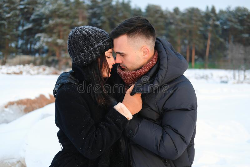 Κλείστε επάνω το πορτρέτο του νέου ελκυστικού ερωτευμένου αγκαλιάσματος ζευγών υπαίθριου στο χειμερινό πάρκο Αισθησιακοί τρυφεροί στοκ φωτογραφίες