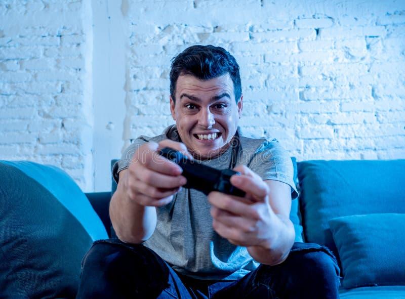 Κλείστε επάνω το πορτρέτο του νεαρού άνδρα που παίζει το τηλεοπτικό παιχνίδι που εθίζεται τη νύχτα σε το που έχει τη διασκέδαση στοκ εικόνες
