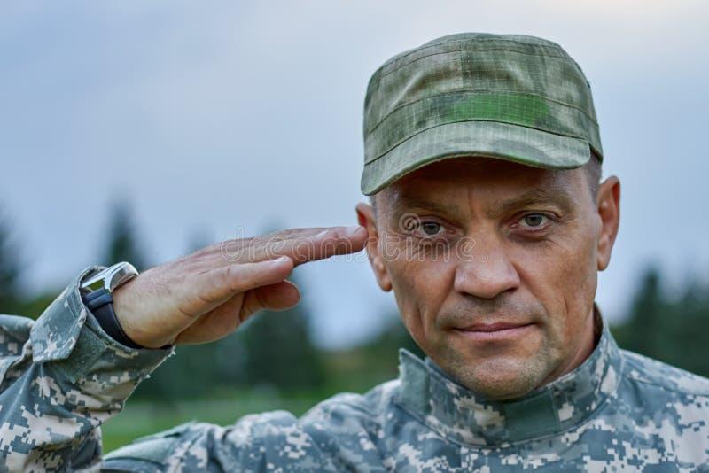 Κλείστε επάνω το πορτρέτο του σοβαρού χαιρετισμού στρατιωτών στοκ εικόνα