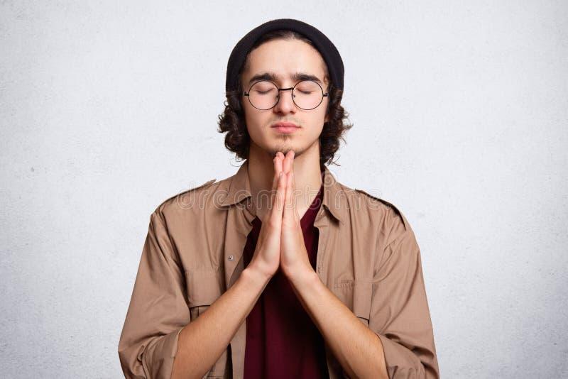 Κλείστε επάνω το πορτρέτο του συγκεντρωμένου ατόμου κρατά τους φοίνικες πιεσμένους μαζί, meditates, προσπαθεί να συλλέξει με τις  στοκ φωτογραφία με δικαίωμα ελεύθερης χρήσης