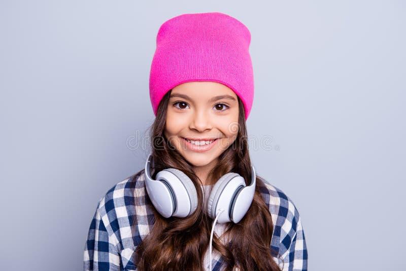 Κλείστε επάνω το πορτρέτο του χαριτωμένου γοητευτικού μικρού κοριτσιού που έχει τα ακουστικά στοκ εικόνα