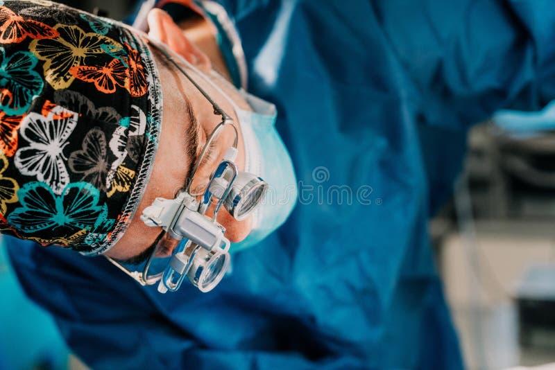 Κλείστε επάνω το πορτρέτο του χειρουργικού γιατρού που εκτελεί τη λειτουργία στο δωμάτιο χειρουργικών επεμβάσεων Χειρούργος που ε στοκ εικόνα