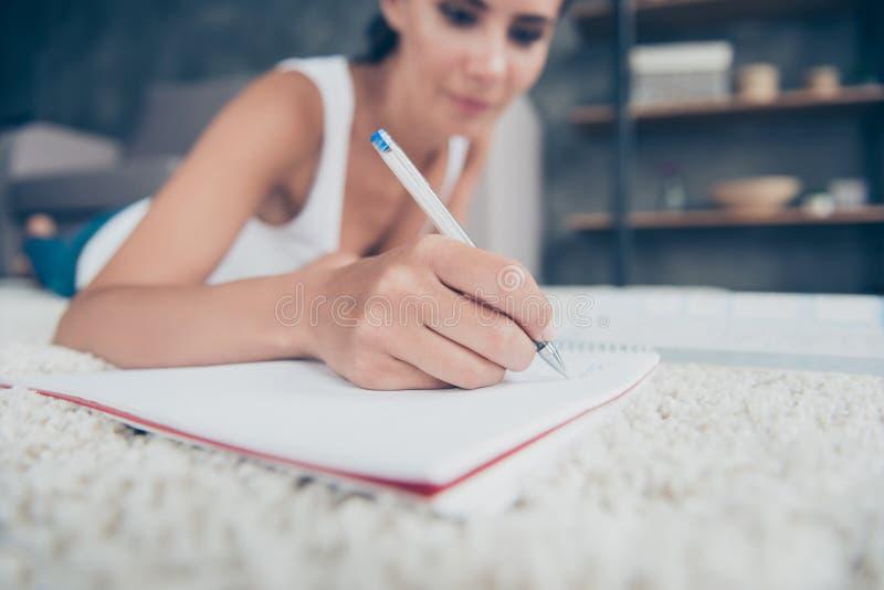 Κλείστε επάνω το πορτρέτο του χεριού γυναικών με το μολύβι γράφοντας στο copybook, στοκ φωτογραφίες με δικαίωμα ελεύθερης χρήσης