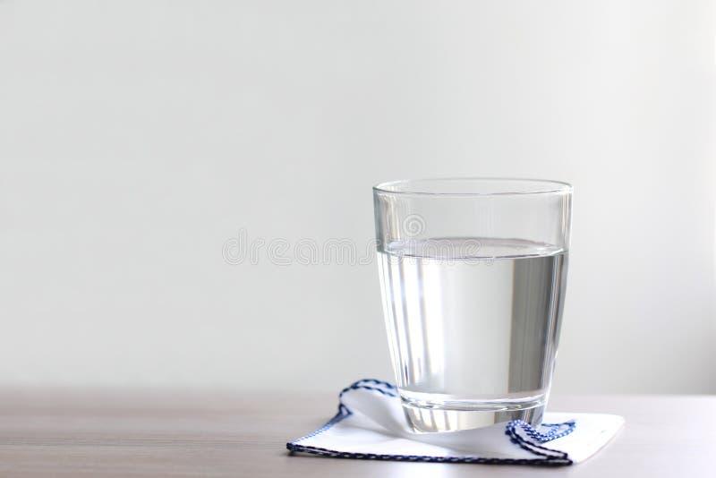 Κλείστε επάνω το ποτήρι του νερού στον πίνακα στοκ εικόνα με δικαίωμα ελεύθερης χρήσης