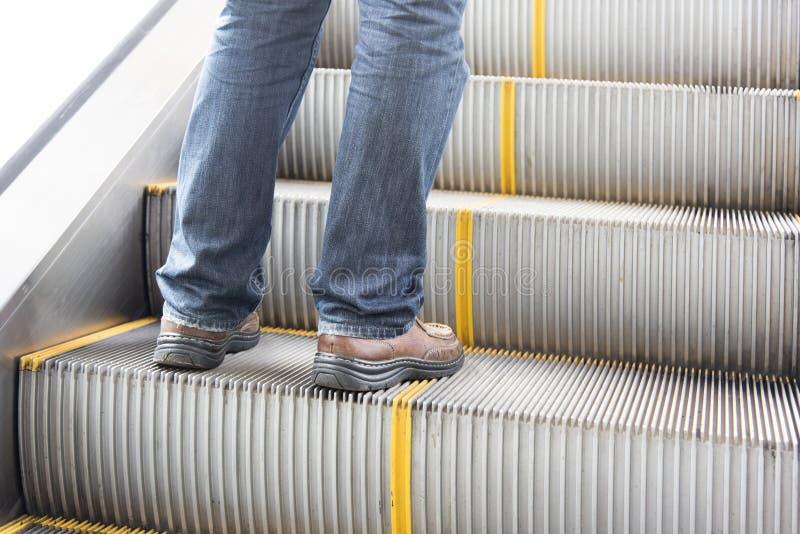 Κλείστε επάνω το πόδι των τζιν ένδυσης ατόμων, παπούτσια δέρματος Στάση στην κυλιόμενη σκάλα στοκ φωτογραφία με δικαίωμα ελεύθερης χρήσης