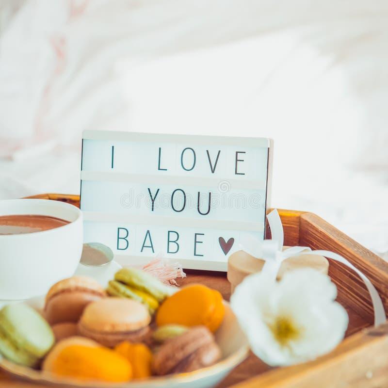 Κλείστε επάνω το ρομαντικό πρόγευμα στο κρεβάτι με σ' αγαπώ το κείμενο μωρών στο αναμμένο κιβώτιο Φλιτζάνι του καφέ, χυμός, macar στοκ φωτογραφίες