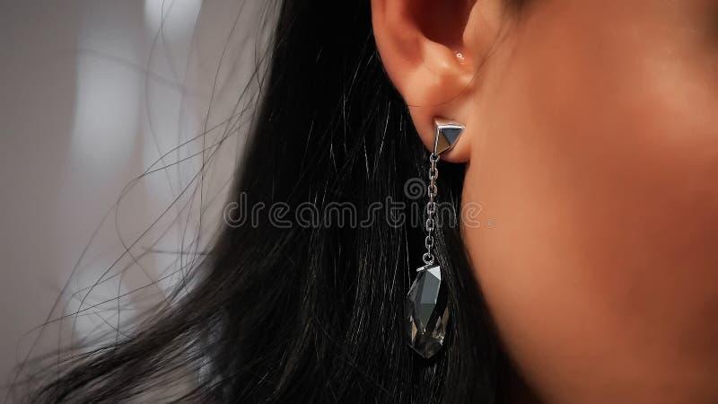 Κλείστε επάνω το σκουλαρίκι στο αυτί της μαύρος-μαλλιαρής γυναίκας στοκ φωτογραφίες