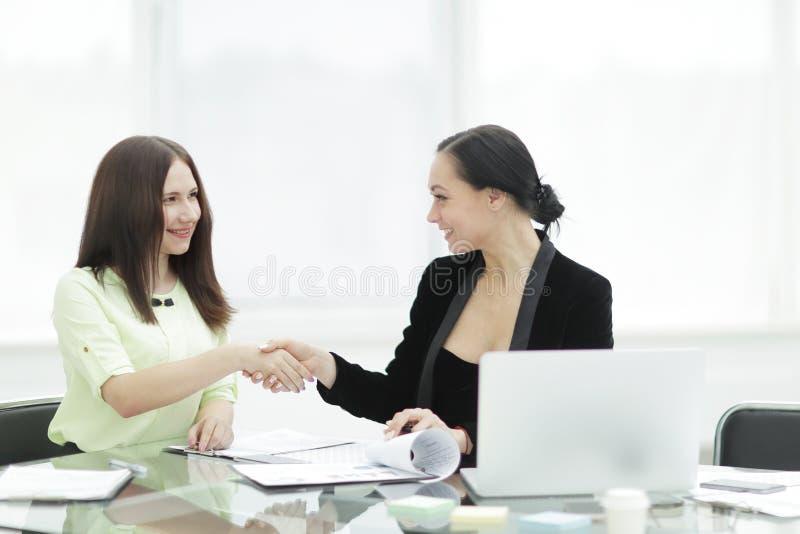 κλείστε επάνω το τίναγμα δύο επιχειρησιακών γυναικών δίνει το ένα το άλλο που κάθεται στο γραφείο στο γραφείο στοκ εικόνες