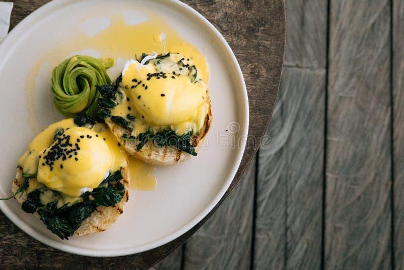 Κλείστε επάνω το υγιές πρόγευμα με τη φρυγανιά ψωμιού και το λαθραίο αυγό με το σπανάκι, αβοκάντο στον ξύλινο κατασκευασμένο πίνα στοκ εικόνα με δικαίωμα ελεύθερης χρήσης