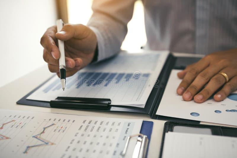 Κλείστε επάνω το χέρι ενός επιχειρηματία που κρατά μια μάνδρα δείχνοντας τη γραφική παράσταση των οικονομικών καταστάσεων ή των κ στοκ εικόνες