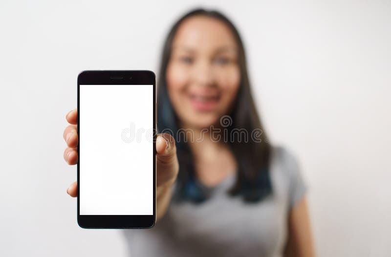 Κλείστε επάνω το χέρι κρατώντας το μαύρο τηλέφωνο στην άσπρη πορεία ψαλιδίσματος μέσα στοκ εικόνες