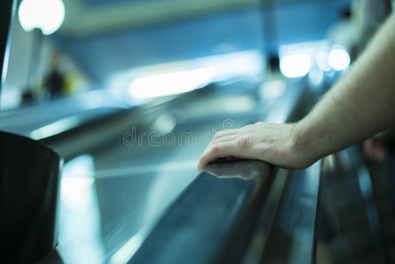 Κλείστε επάνω το χέρι προσώπων ` s που κινείται επάνω στην κυλιόμενη σκάλα στοκ φωτογραφία με δικαίωμα ελεύθερης χρήσης