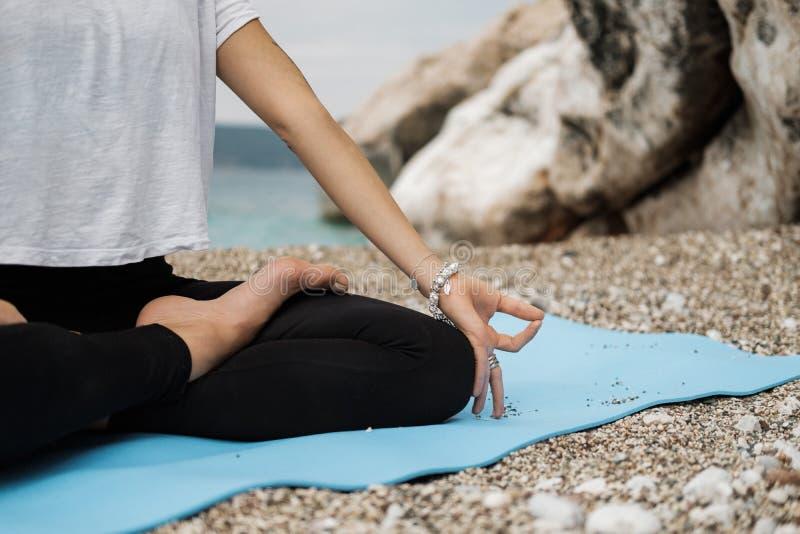 Κλείστε επάνω το χέρι της γυναίκας που κάνει μια υπαίθρια θέση γιόγκας Lotus και στοκ εικόνες