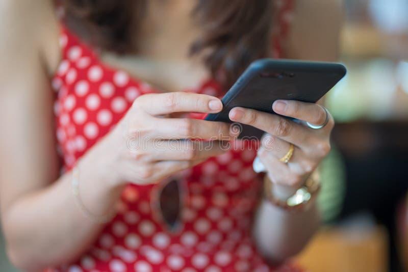 Κλείστε επάνω το χέρι του παιχνιδιού έννοιας γυναικών με το έξυπνο τηλέφωνο στο ξύλινο επιτραπέζιο υπόβαθρο καφέδων στοκ φωτογραφία με δικαίωμα ελεύθερης χρήσης