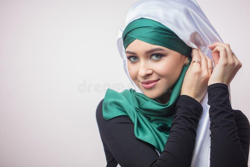 Κλείστε επάνω το όμορφο μουσουλμανικό κορίτσι πορτρέτου OD που επιδεικνύει πώς να δέσει ένα headscarf στοκ εικόνα με δικαίωμα ελεύθερης χρήσης