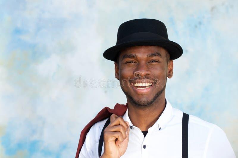 Κλείστε επάνω το όμορφο νέο άτομο αφροαμερικάνων με suspenders και το καπέλο χαμογελώντας από τον τοίχο στοκ εικόνες