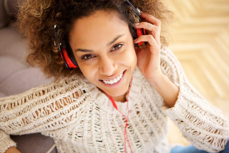 Κλείστε επάνω το όμορφο νέο χαμόγελο γυναικών αφροαμερικάνων με τα ακουστικά στοκ εικόνα με δικαίωμα ελεύθερης χρήσης