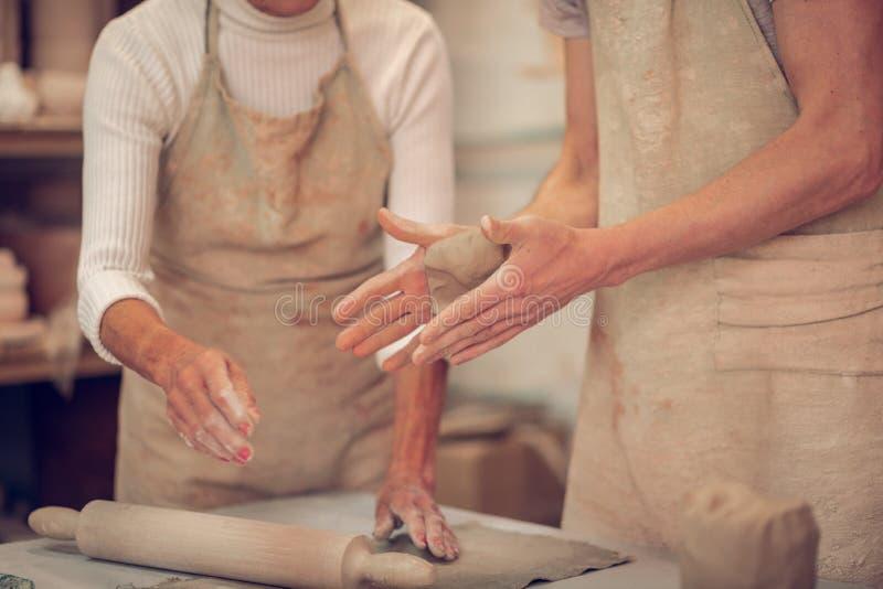 Κλείστε επάνω των αρσενικών χεριών με ένα κομμάτι του αργίλου στοκ φωτογραφία με δικαίωμα ελεύθερης χρήσης