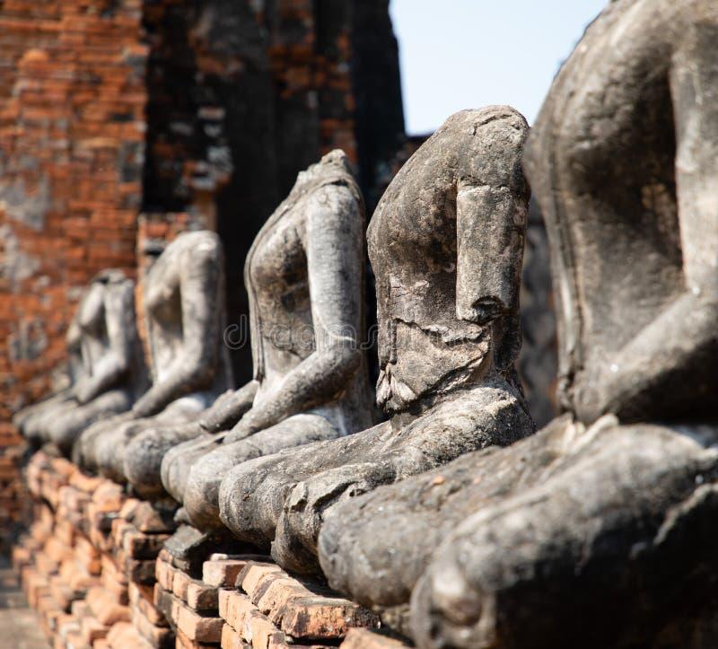 Κλείστε επάνω των αρχαίων αγαλμάτων του Βούδα πετρών που τοποθετούνται στη γραμμή στο ναό σε Ayutthaya στοκ φωτογραφίες