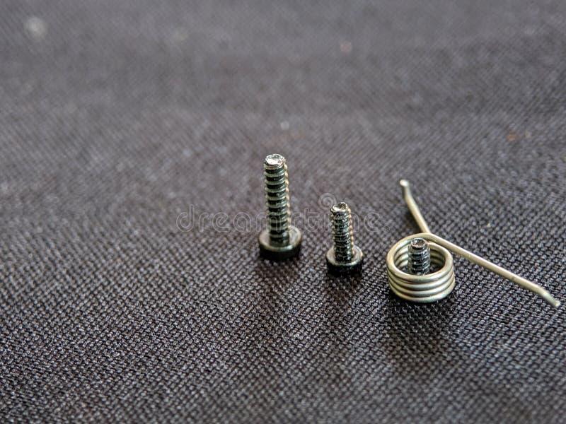 Κλείστε επάνω των βιδών μετάλλων που τακτοποιούνται σύμφωνα με μια βίδα μακρύτερη από άλλες που απομονώνονται πέρα από τη μαύρη σ στοκ εικόνα με δικαίωμα ελεύθερης χρήσης