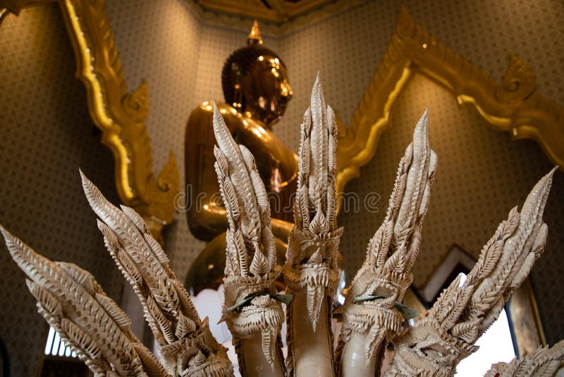 Κλείστε επάνω των δράκων με ένα χρυσό άγαλμα του Βούδα στο υπόβαθρο στοκ εικόνα